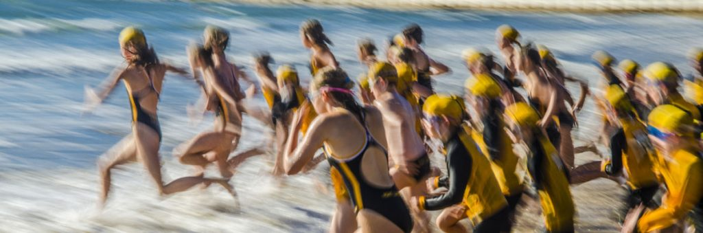 Triathletes running into the water