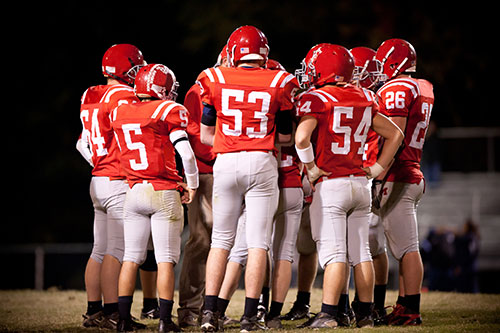 Football Players standing in a huddle